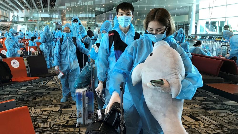 Una mujer vietnamita lleva un animal de peluche mientras aborda un vuelo de repatriación de Singapur a Vietnam en medio de la propagación del brote de la enfermedad por coronavirus (COVID-19) en el aeropuerto de Changi, Singapur