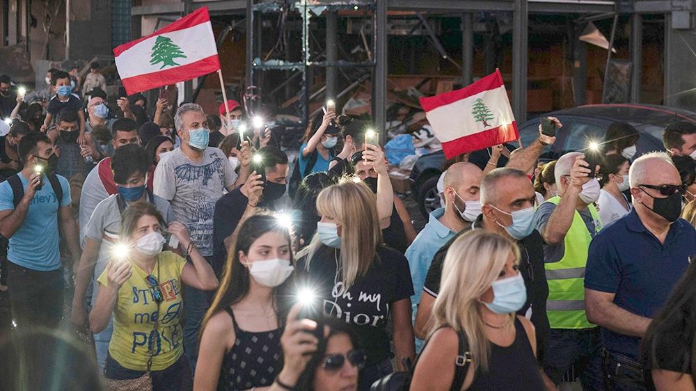 Οι διαδηλωτές περνούν από ένα κατεστραμμένο κτίριο που κρατά κεριά και φακούς προς τιμήν των θυμάτων της θανατηφόρας έκρηξης στο λιμάνι της Βηρυτού που κατέστρεψε μεγάλα τμήματα της πρωτεύουσας, στη Βηρυτό του Λιβάνου,