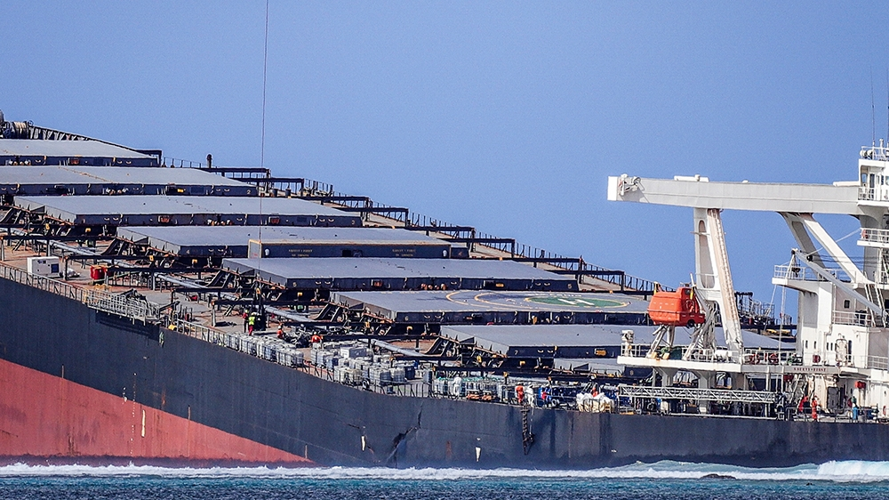 A helicopter hovers over the vessel MV Wakashio, belonging to a Japanese company but Panamanian-flagged, that ran aground and caused oil leakage near Blue bay Marine Park in southeast Mauritius on Aug