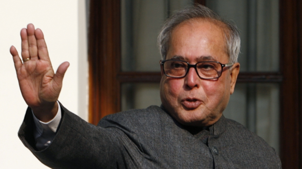 Indian Foreign Minister Mukherjee waves to the media in New Delhi