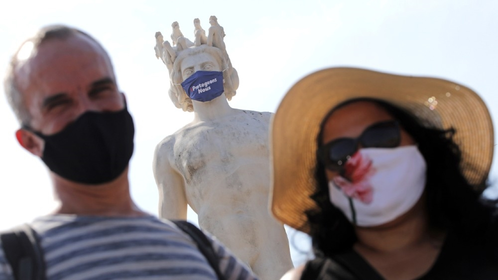 Tourists in protective masks stand by a masked statue that reads,