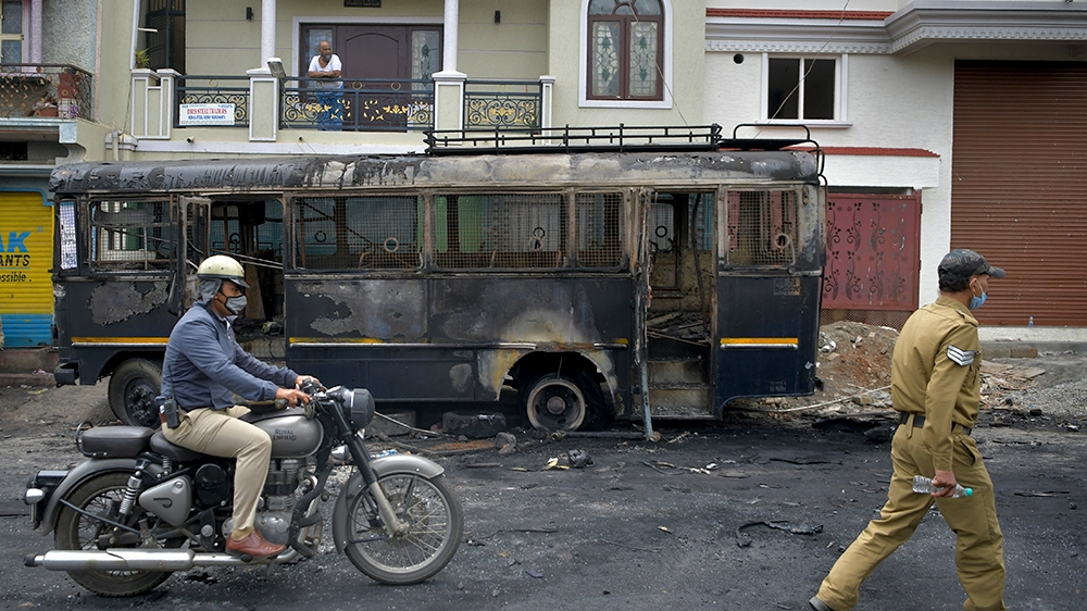 A policeman rides past a burnt police vehicle in Bangalore on August 12, 2020, after violence broke out overnight in Devara Jevana Halli area following a