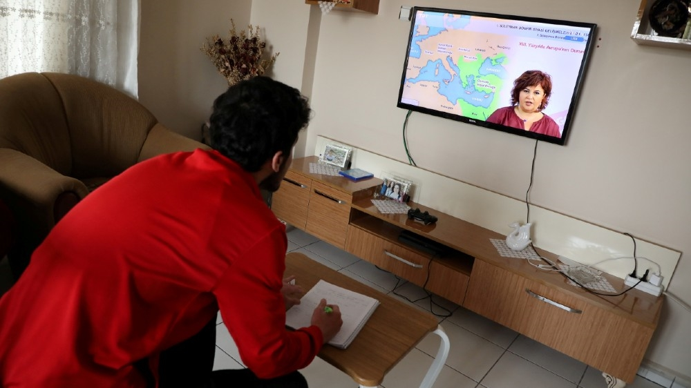 FILE PHOTO: Sinan Guldure, a 16-year old high school student, watches a history leasson on television as part of home schooling during the coronavirus disease (COVID-19) outbreak,