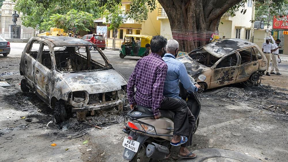 Automobiliste ware laanscht verbrannt Autoen zu Bangalore den 12. August 2020, nodeems d'Gewalt an der Regioun Devara Jevana Halli ausgebrach ass no engem
