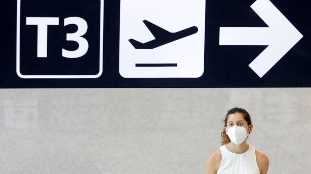 A passenger wearing a protective face mask walks at Fiumicino Airport, one of the two airports in the world to obtain the 'Biosafety Trust certification' for the correct application o