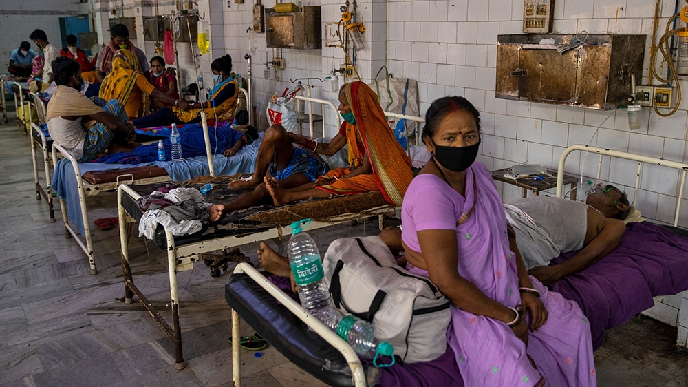 COVID-19 patient Parsada Sah, 67, a shopkeeper, lies on a hospital bed as his wife Vimla Devi, 62, sits next to him in the emergency ward as they wait for Sah to be transferred to the Intensive Care U