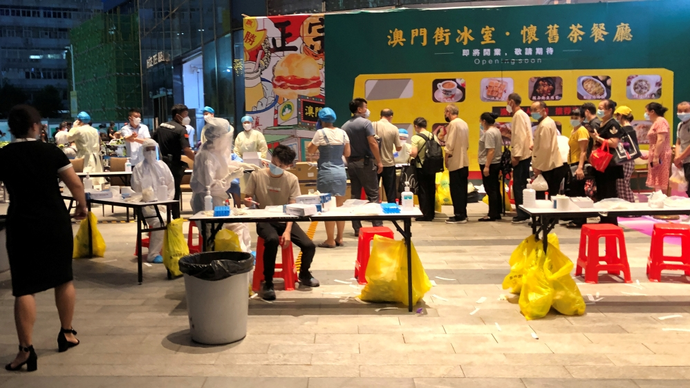 Medical workers wearing protective suits are seen at a nucleic acid testing site outside the IBC Mall in Shenzhen