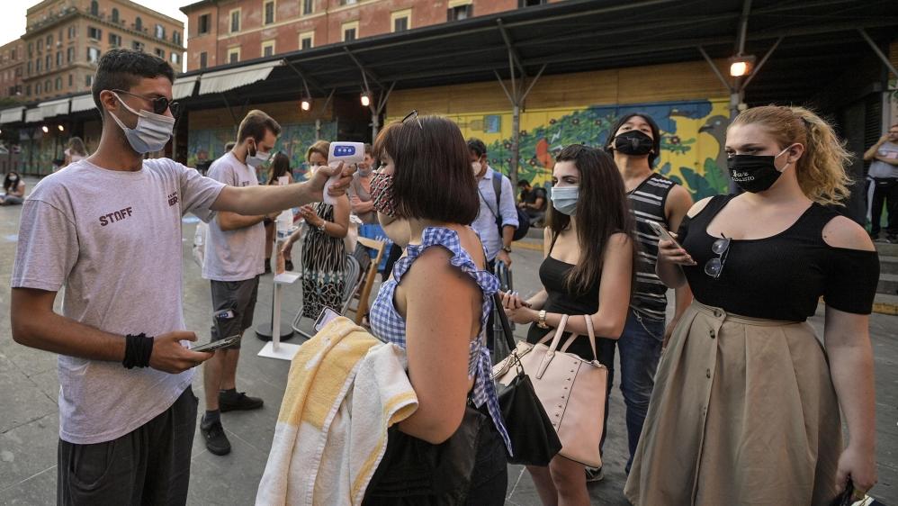 Un travailleur portant un masque facial (L) vérifie la température corporelle des spectateurs pour d'éventuelles infections par le coronavirus SRAS-CoV-2 qui provoque la maladie pandémique COVID-19 à l'ouverture n