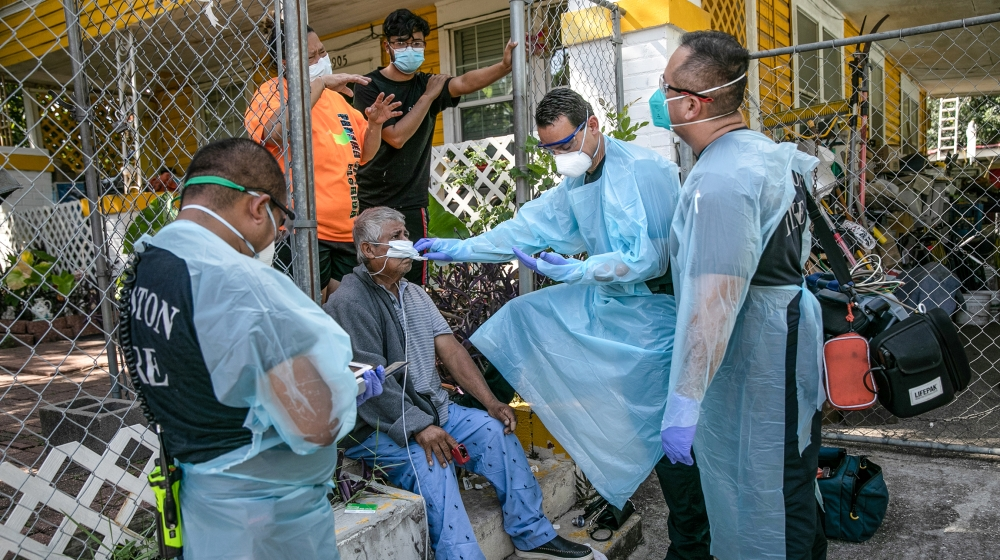 An EMS medic checks the temperature of a possible Covid-9 patient before transporting him to the hospital on August 13, 2020 in Houston, Texas. Several of the man's family members had also tested posi