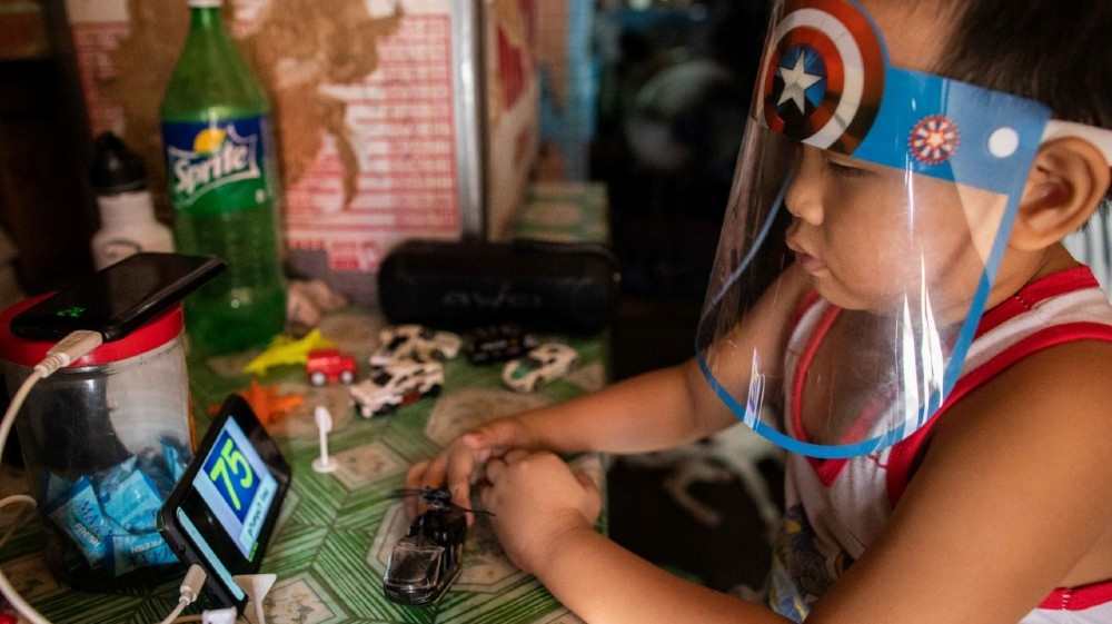 A boy wears a face shield while watching a simulation of an online learning class from a smartphone in his home, amid the coronavirus disease (COVID-19) outbreak in Manila, Philippines,