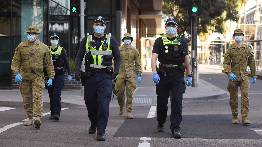 A group of police and soldiers patrol the Docklands area of Melbourne on August 2, 2020, after the announcement of new restrictions to curb the spread of the COVID-19 coronavirus. - Australia on Augus