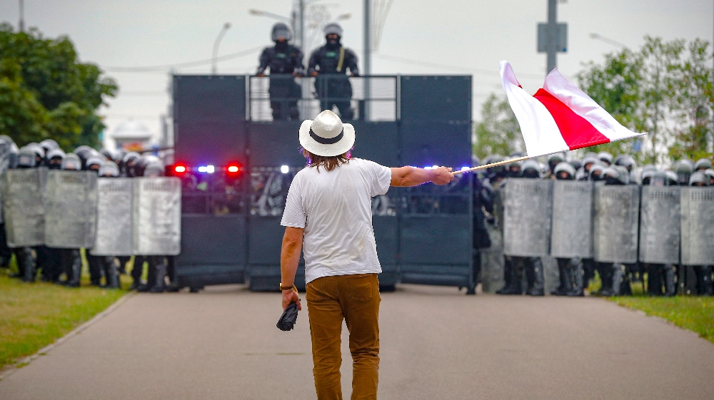 A man waves a historical Belarus flag in front of a riot police blockade during a protest in Minsk, Belarus, Sunday, Aug. 23, 2020. Demonstrators are taking to the streets of the Belarusian capital