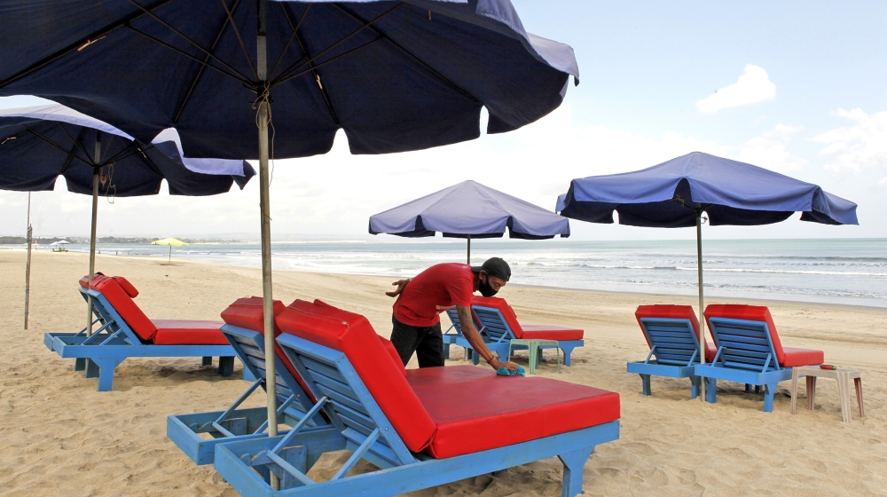 A worker cleans chairs for rent as beaches are reopening following months of lockdown due to the new coronavirus outbreak, in Bali, Indonesia, Monday, July 27, 2020. The Indonesia Health ministry anno