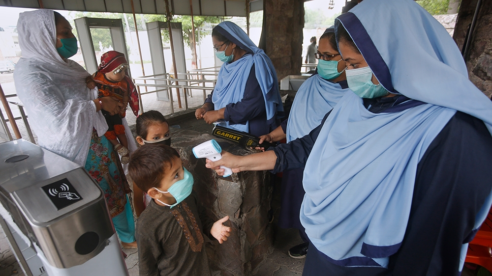 A worker checks the temperature of children arriving with their mother to visit the zoo, following an ease in restrictions that had been imposed to help control the coronavirus, in Lahore, Pakistan, T