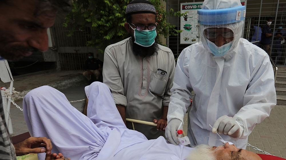 A health worker takes a nasal swab sample of an elderly man at a testing and screening facility for the new coronavirus, in a hospital in Karachi, Pakistan, Friday, July 17, 2020. (AP Photo/Fareed Kha