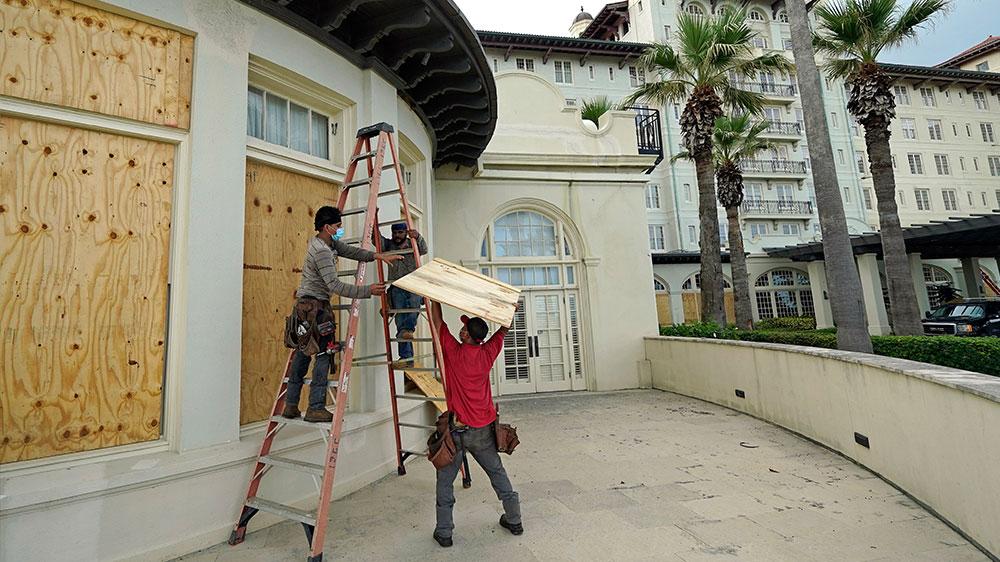 Trabajadores tapan las ventanas antes del huracán Laura
