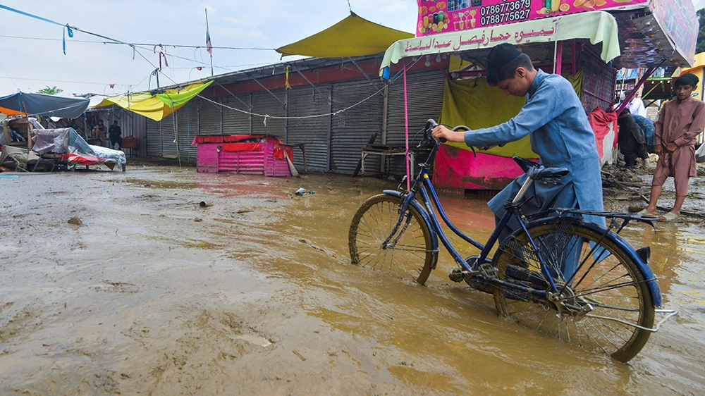 A flash flood affected villager pushes a bicycle along a road in Charikar, Parwan province, on August 26, 2020. - At least 46 people have been killed and hundreds of houses destroyed by flash floods a