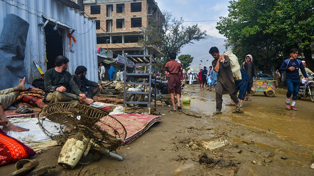 People go around a market area after a flash-flood in Charikar, Parwan province, on August 26, 2020. - At least 46 people have been killed and hundreds of houses destroyed by flash floods as torrentia