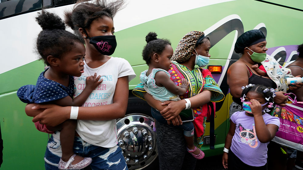 Personas hacen fila para abordar autobuses para evacuar antes del huracán Laura