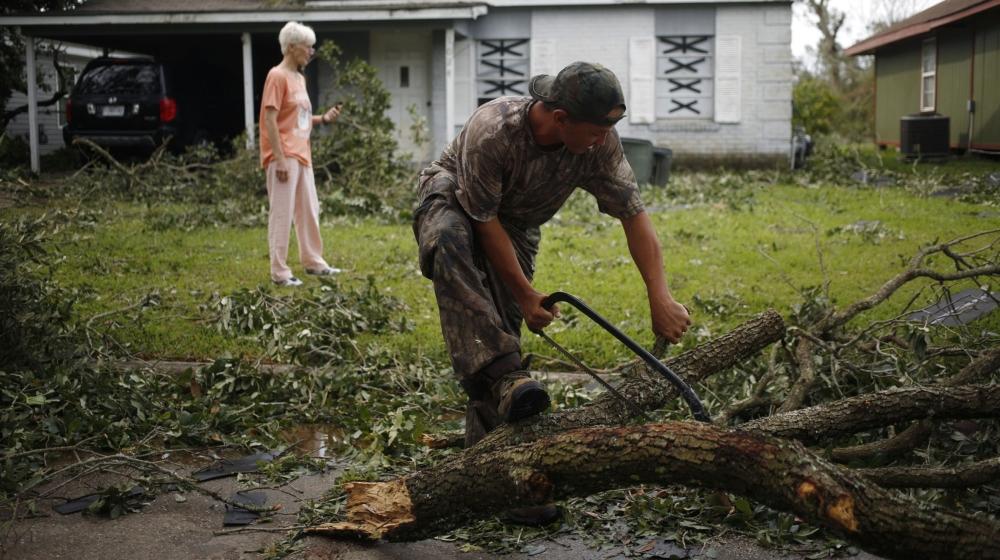 Ένας άντρας χρησιμοποιεί ένα πριόνι για να κόψει ένα άκρο δέντρου κατεβασμένο μετά την πτώση του τυφώνα Laura στη λίμνη Charles, Λουιζιάνα, ΗΠΑ, την Πέμπτη 27 Αυγούστου 2020. Ο τυφώνας Laura έσπασε σε όλη τη Λουιζιάνα νωρίς την Πέμπτη, β