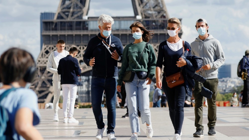 People wearing protective masks walk at the Trocadero square near the Eiffel Tower as France reinforces mask-wearing as part of efforts to curb a resurgence of the coronavirus disease