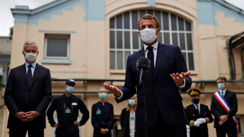French President Emmanuel Macron, wearing a protective face mask, delivers a speech as he visits a site of pharmaceutical group Seqens, a global leader on the production of active