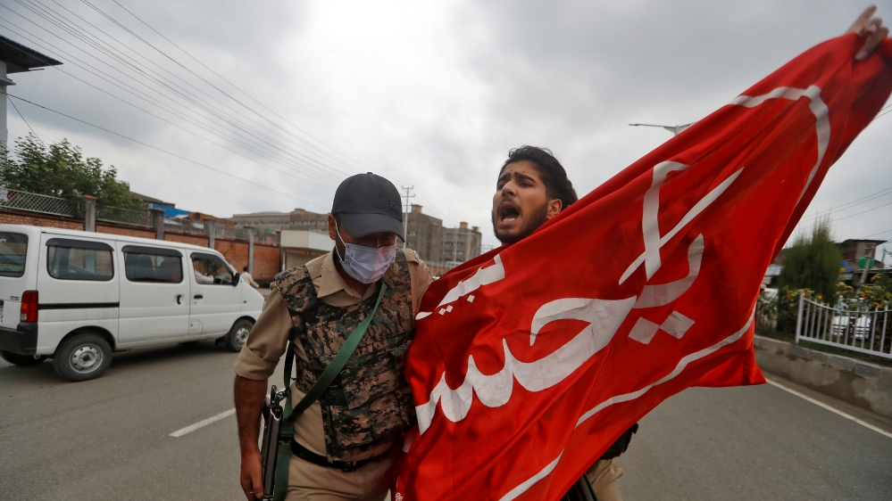 A Kashmir Shi'ite Mulsim shouts slogans as he is detained an Indan policeman while trying to participate in a Muharram procession, in Srinagar