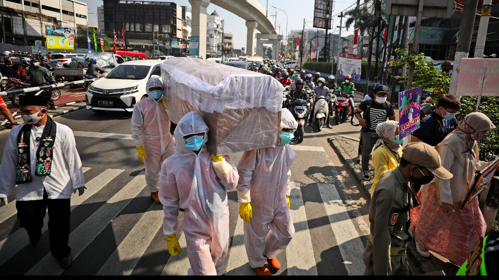 Government officials in protective suits carry a mock coffin as they walk around a busy intersection during a coronavirus awareness campaign to remind people of the risk of contracting COVID-19