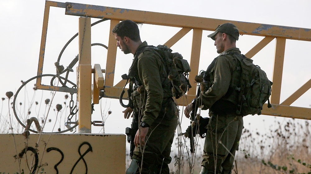 Israeli soldiers man a position on a road leading to the Syrian border, near the location where the army said it killed four men laying explosives at a security fence along the Israeli-occupied sector