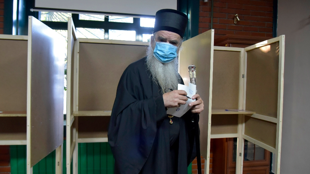 Serbian Orthodox bishop Amfilohije wearing a mask against the spread of the coronavirus prepares to vote in parliamentary elections at a polling station in Cetinje, south of Podgorica, Montenegro,