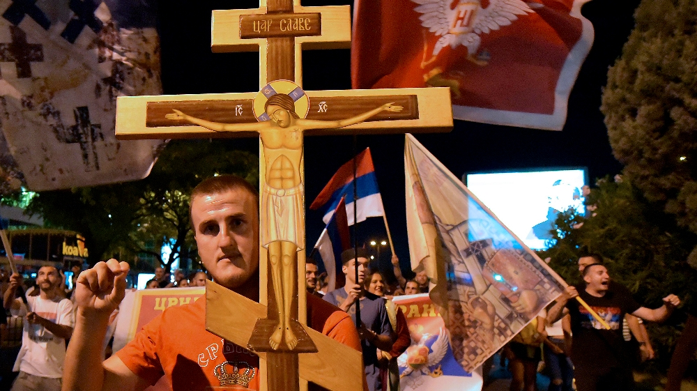 An opposition supporter holds a cross during church-led protest in Podgorica, Montenegro, Thursday, Aug. 27, 2020. Montenegro is holding a parliamentary election this weekend