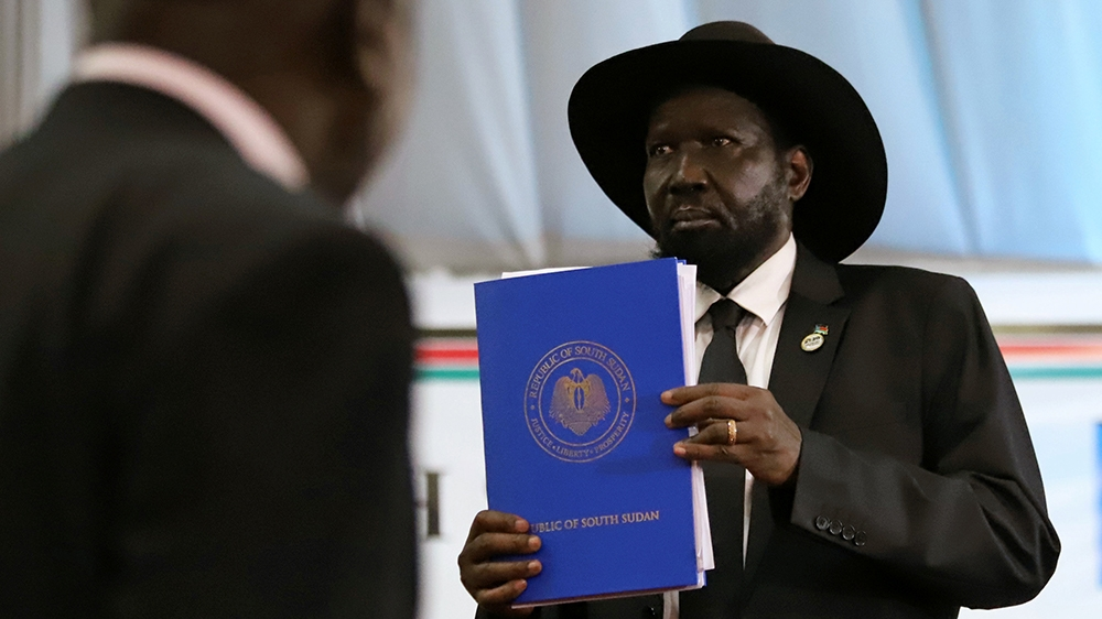 South Sudan's President Salva Kiir Mayardit holds a copy of a signed peace agreement between Sudan and five key rebel groups, a significant step towards resolving deep-rooted conflicts that raged unde