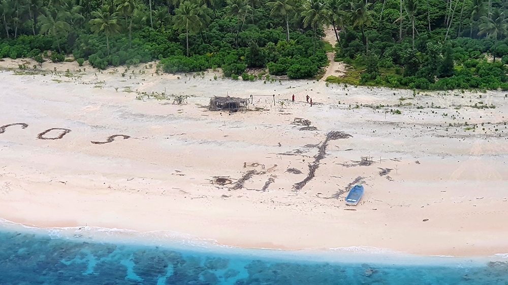Three rescued from tiny Pacific island after writing SOS in sand thumbnail
