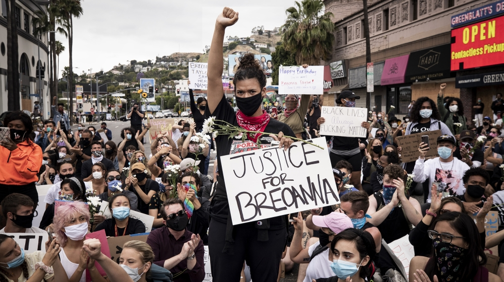 A protester raises her fist while holding a placard reading 'Justice for Breonna' during a gathering to celebrate the birthday of Breonna Taylor amid demonstrations over the arrest in Minnesota of Geo