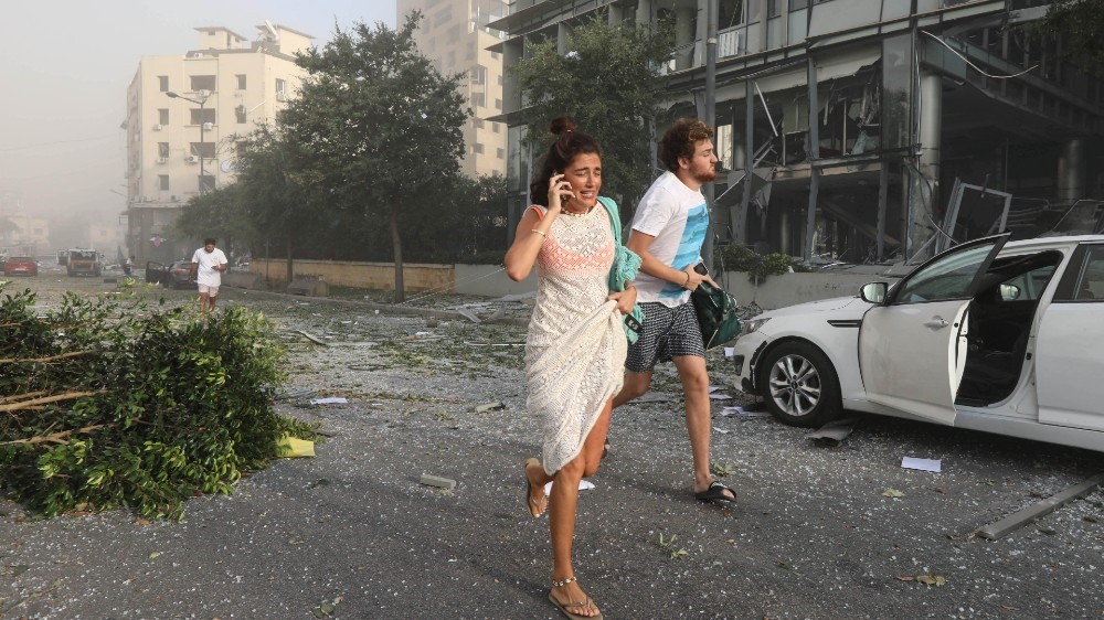 People run for cover following an explosion in Beirut's port area