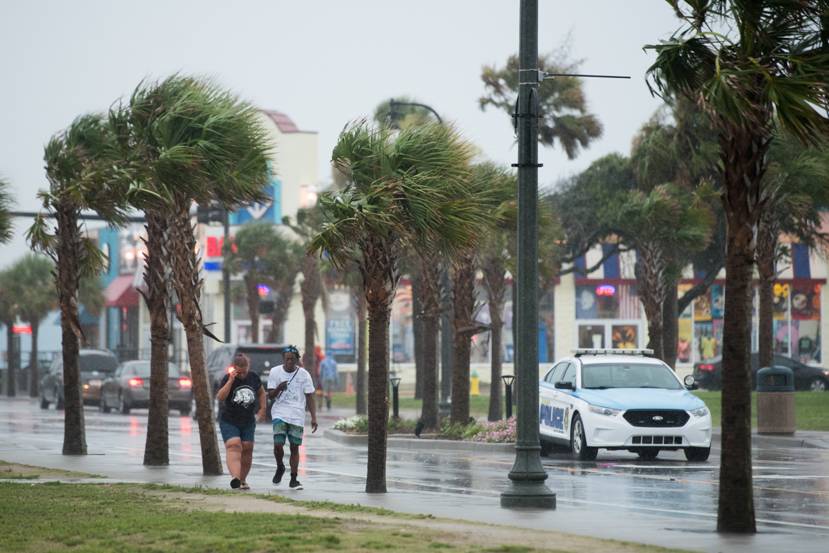People walk along Ocean Boulevard in the rain in Myrtle Beach, South Carolina. Hurricane Isaias continued to move north along the United States' Eastern Seaboard. [Sean Rayford/Getty Images]