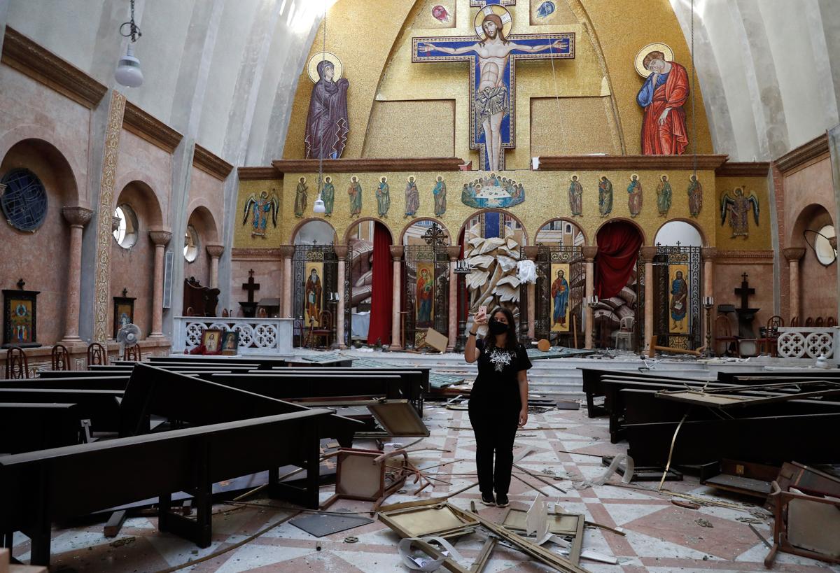Një grua fotografon me celularin e saj për një kishë të dëmtuar, pas një shpërthimi ra në portin e Bejrutit.  [Hussein Malla / Fotografia e AP]