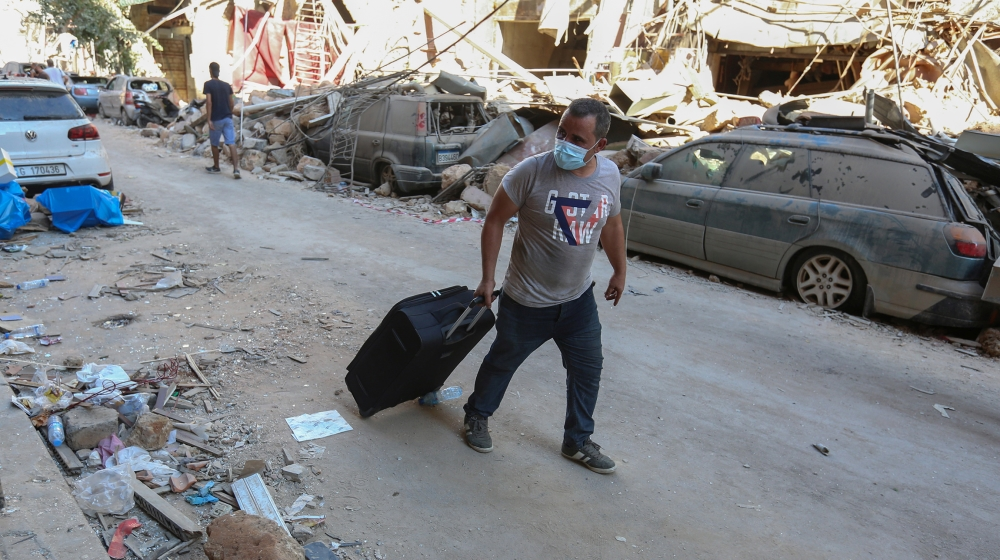 A man pushes his belongings along a street as he evacuates his damaged house, following Tuesday's blast in Beirut's port area, Lebanon August 5, 2020. REUTERS/Aziz Taher