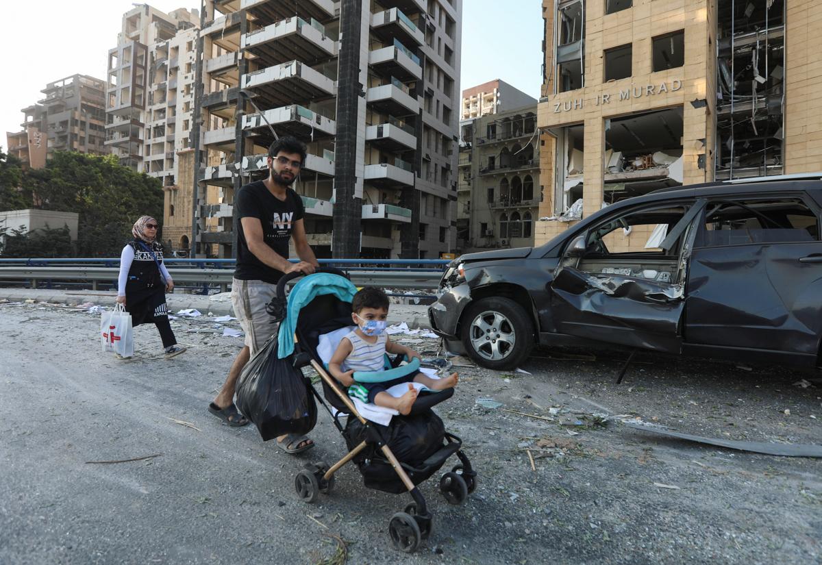 Një burrë shtyn një shëtitës me një fëmijë përpara një automjeti të dëmtuar pranë vendit të shpërthimit të së martës në zonën e portit të Bejrutit.  [Mohamed Azakir / Reuters]