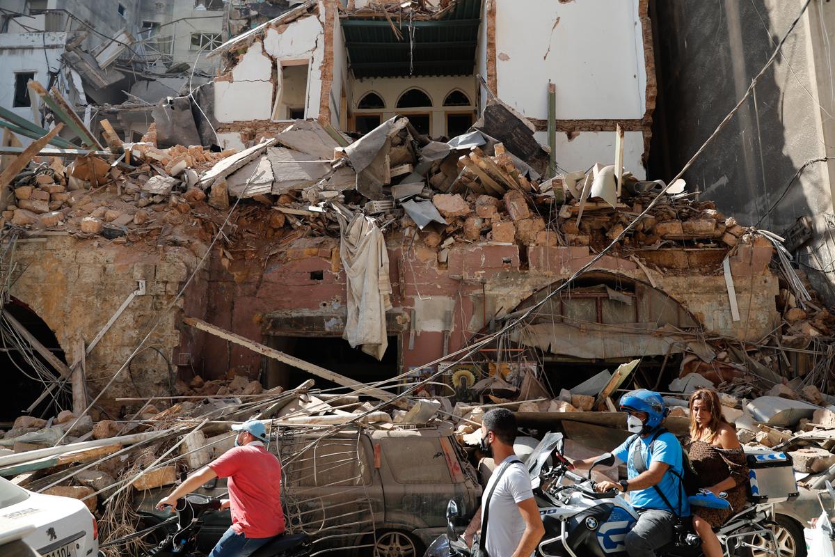 Qytetarët ngasin skuterat e tyre dhe motoçikletat kalojnë para një shtëpie që u shkatërrua në shpërthimin masiv të së martës në portin e Bejrutit.  [Hussein Malla / Fotografia e AP]