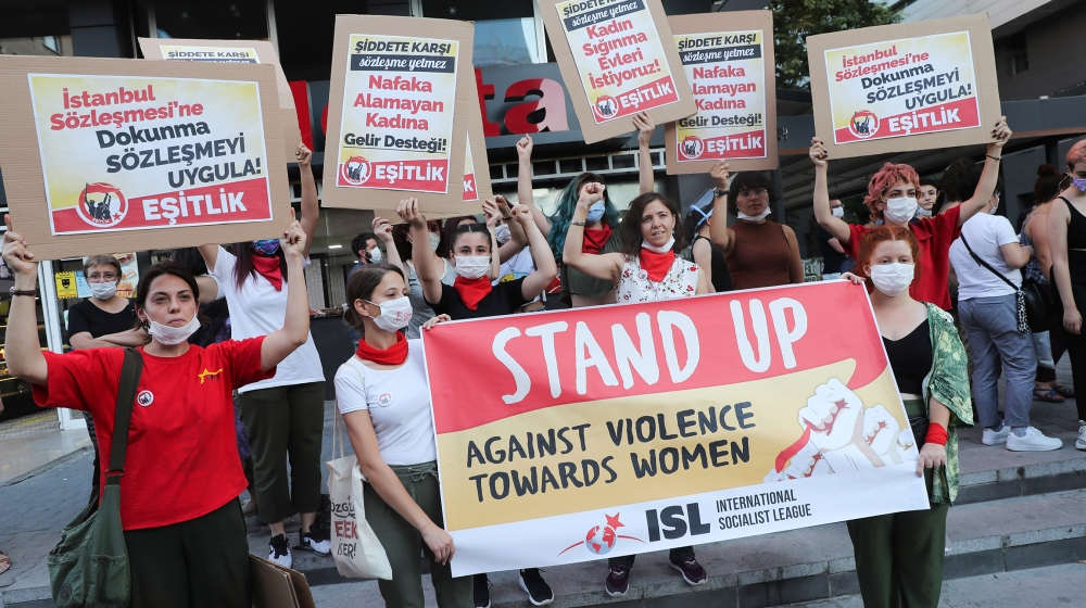 Women wearing face masks hold signs in Ankara, on August 5, 2020, during a demonstration to demand the government does not withdraw from the Istanbul Conventio, a landmark treaty, on preventing domest