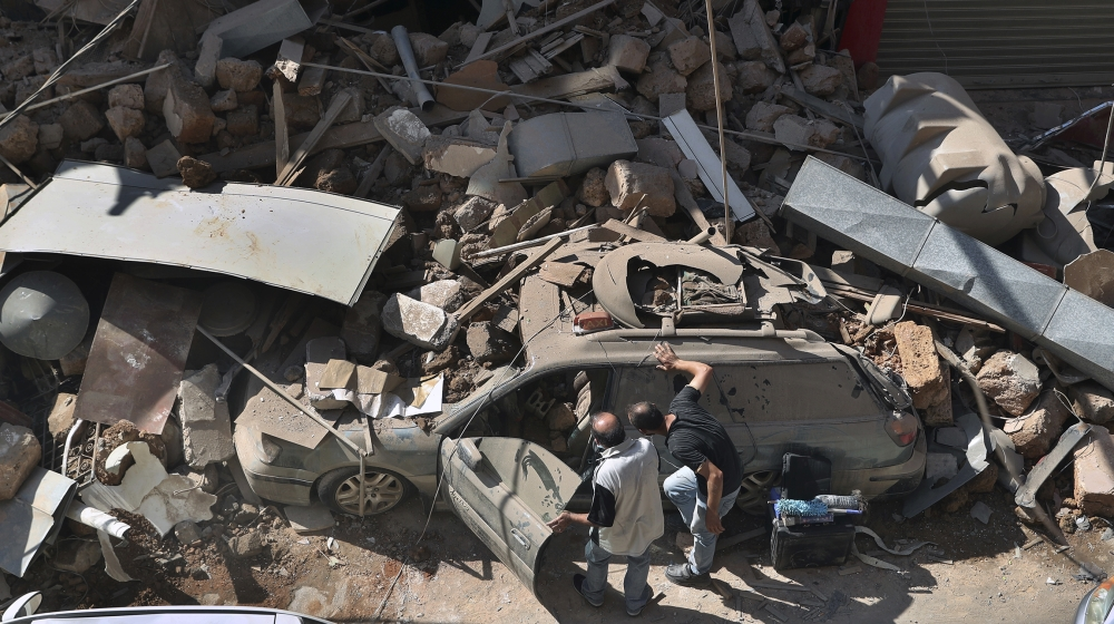 People inspect their car that was damaged in Tuesday's massive explosion in the seaport of Beirut, Lebanon, Wednesday, Aug. 5, 2020. The explosion flattened much of a port and damaged buildings acros