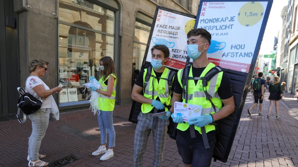 People wearing yellow vests hand out masks and information brochures where to wear the mandatory masks in the busiest streets of the city, during the coronavirus disease (COVID-19)