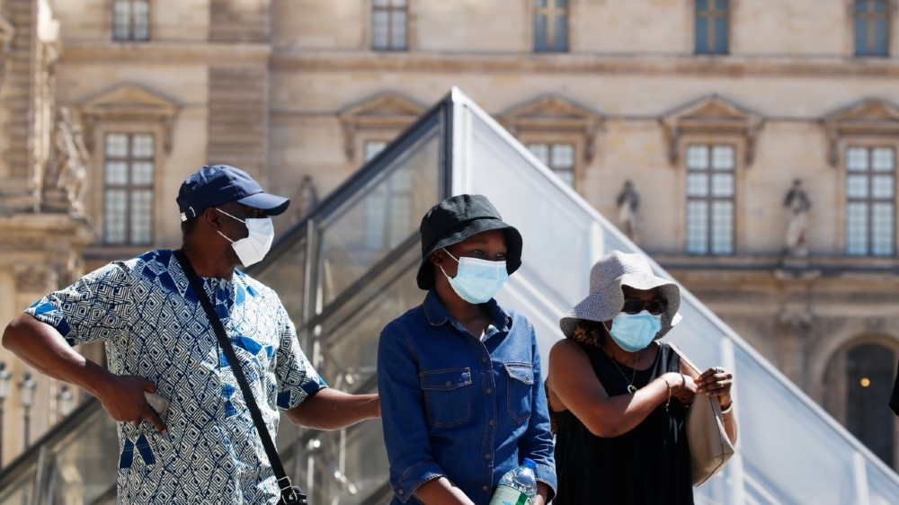 People wearing protective masks walk near the Louvre Museum as France reinforces mask-wearing as part of efforts to curb a resurgence of the coronavirus disease (COVID-19)