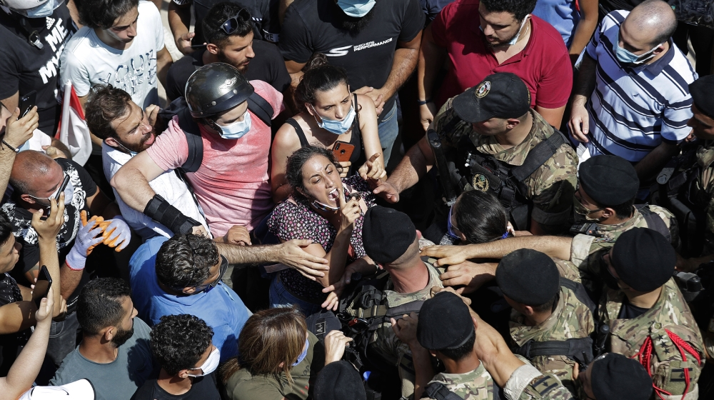 A woman yells at Lebanese soldiers during scuffles with the soldiers who are blocking a road as French President Emmanuel Macron visits the Gemmayzeh neighborhood, which suffered extensive damage from