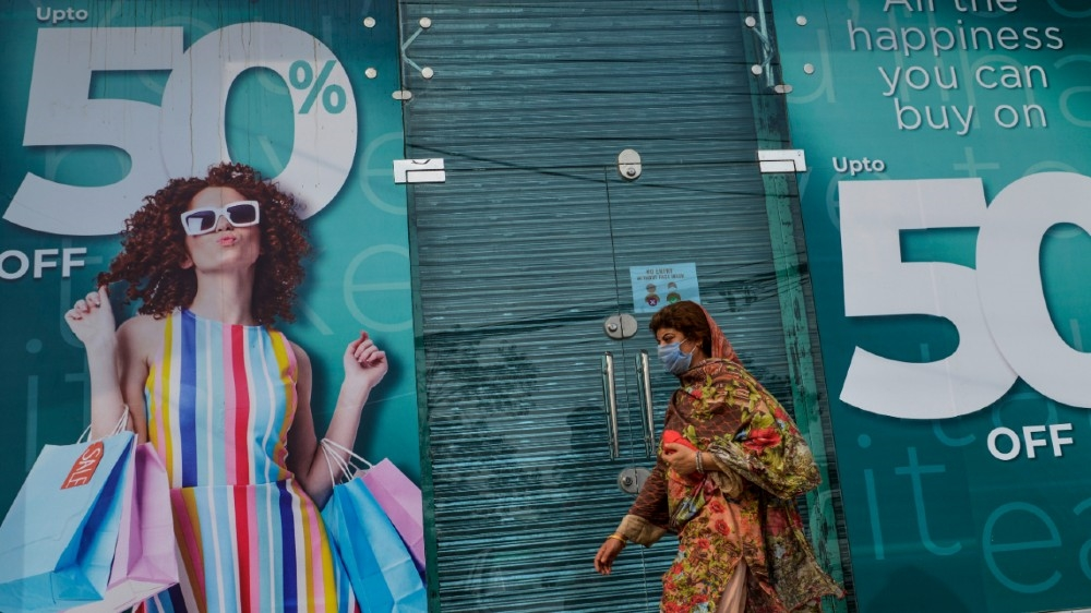 A woman walks past a shuttered market in Rawalpindi on July 29, 2020, after the Punjab province government announced a lockdown closing markets, shopping malls and