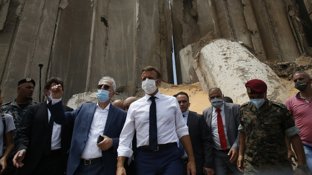French President Emmanuel Macron, center, visits the devastated site of the explosion at the port of Beirut, Lebanon, Thursday Aug.6, 2020. French President Emmanuel Macron has arrived in Beirut to of