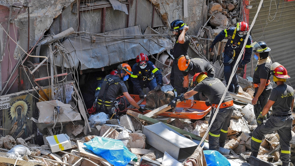 Members of the Lebanese civil defence use a dog to search for victims and survivors under the rubble of a building in the Gemayzeh neighbourhood on August 6, 2020, two days after a massive explosion i