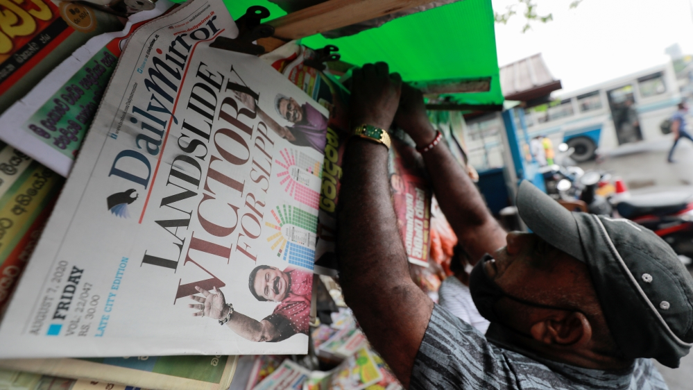 A man hangs newspapers carrying  headlines about the victory of Mahinda Rajapaksa's Sri Lanka People's Front party in the country's parliamentary election in Colombo