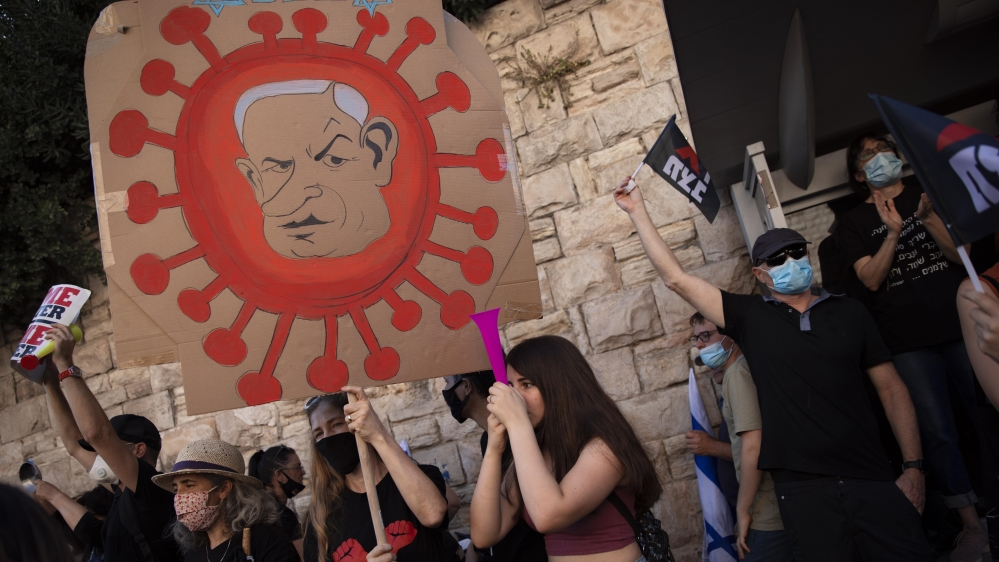 A protester holds a sign depicting Prime Minister Benjamin Netanyahu